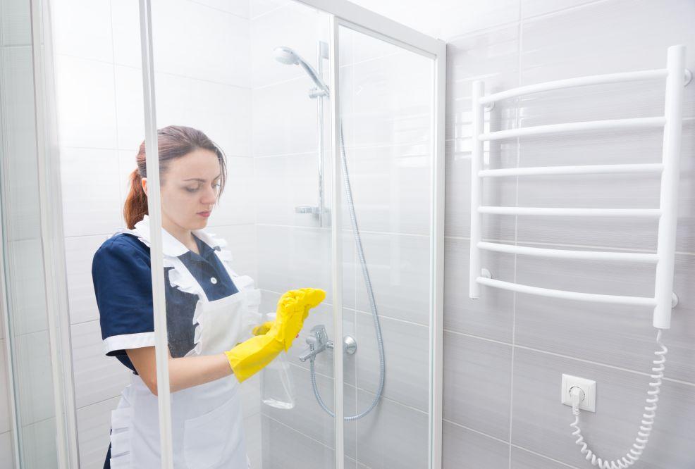 Donna che pulisce il box della doccia