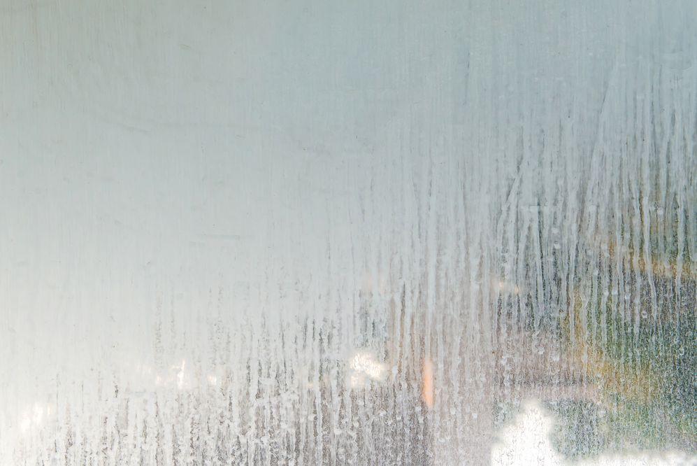 Un vetro della doccia sporco di incrostazioni di calcare